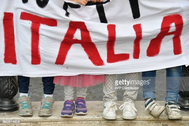 Children hold a banner reading 'Italy' on October 13 2017 in front of the Italian Parliament in Rome during a protest of the association 'Italiani...