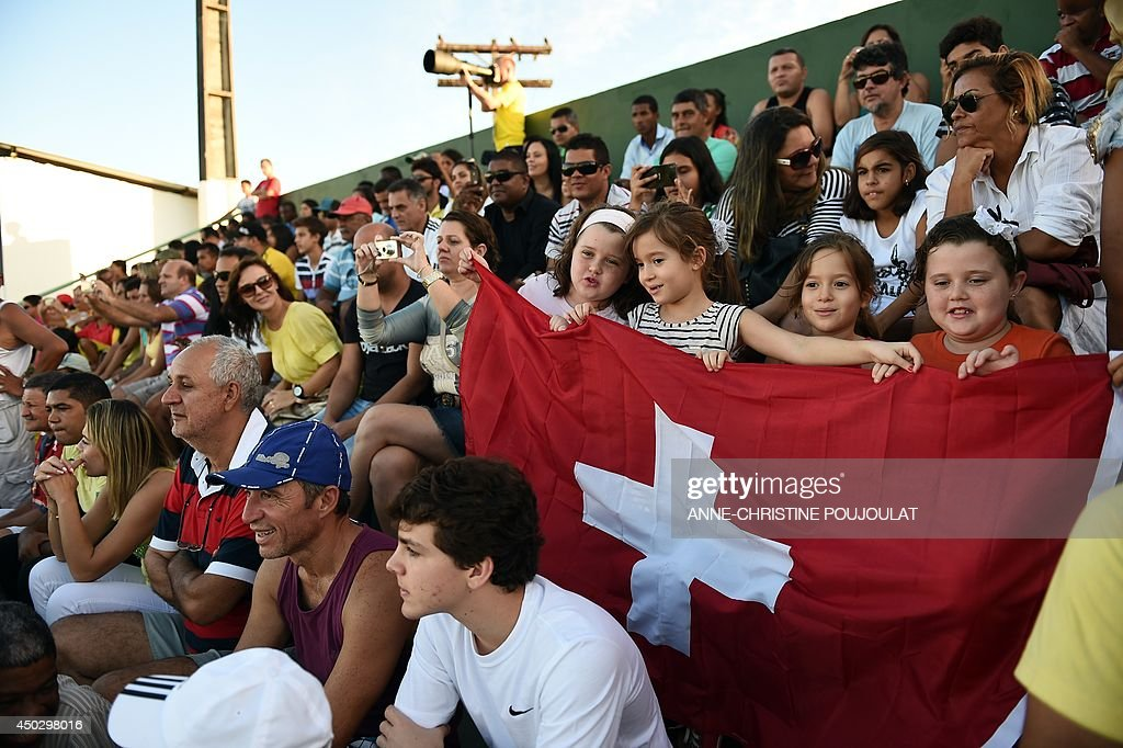 Children hold a Swiss flag during the Switzerland national football team training session on June 8, 2014 at the Municipal Stadium in Porto Seguro, prior to the start of the 2014 FIFA World Cup in Brazil.