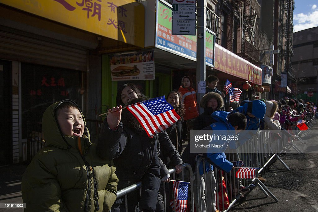 Children hold American flags during the 14th Annual Chinatown Lunar New Year Parade on February 17, 2013 in New York City. This year celebrates the Year of the Snake.