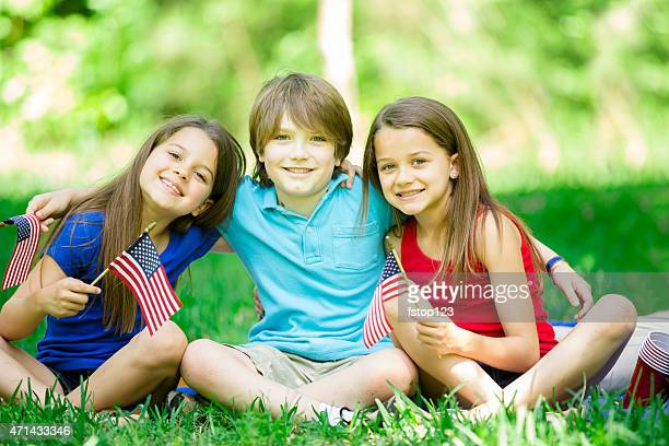 Children hold American flags outdoors, summer. Memorial Day, July 4th.