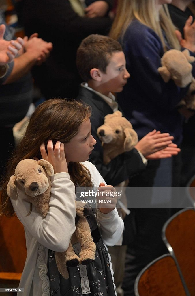 Children hold cuddly toy dogs, handed out by the Red Cross at the entrance, at a memorial service for the victims of the Sandy Hook Elementary School shooting on December 16, 2012 in Newtown, Connecticut. US President Barack Obama will address the memorial for the twenty-six people, 20 of them children, who were killed when a gunman entered Sandy Hook Elementary and began a shooting spree. AFP PHOTO/Mandel NGAN
