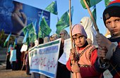 Children hold flags as women supporters of Pakistani political and Islamic party JammateIslami stage a protest against the Taliban militants attack...