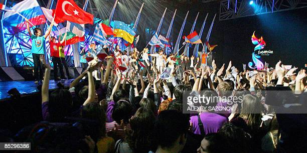Children hold flags of the Eurovision music contest participants as they sing during the Russian qualification contest of Eurovision in Moscow on...