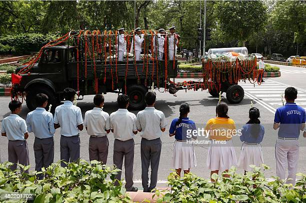 Children hold flowers as they wait to pay tribute to former Indian President APJ Abdul Kalam as his body is transported from the Airport to his House...