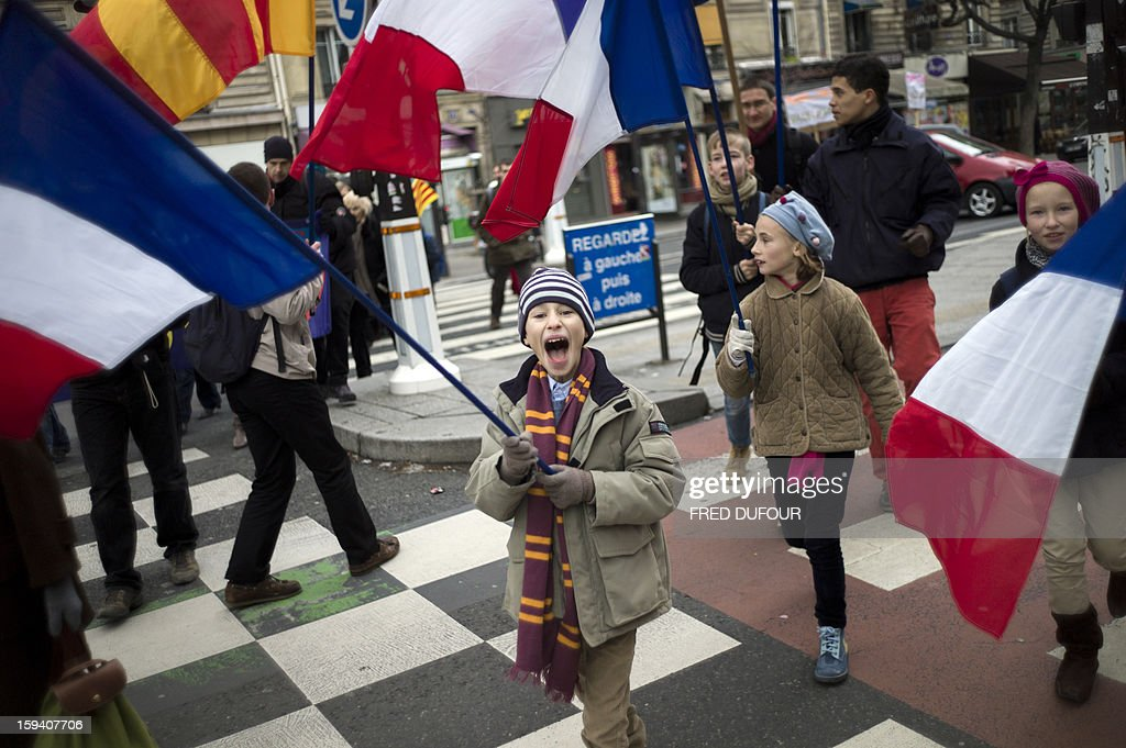 Children hold French national flags as they take part in a march against same-sex marriage on January 13, 2013 in Paris. Tens of thousands march in Paris on January 13 to denounce government plans to legalise same-sex marriage and adoption which have angered many Catholics and Muslims, France's two main faiths, as well as the right-wing opposition. The French parliament is to debate the bill -- one of the key electoral pledges of Socialist President -- at the end of this month.