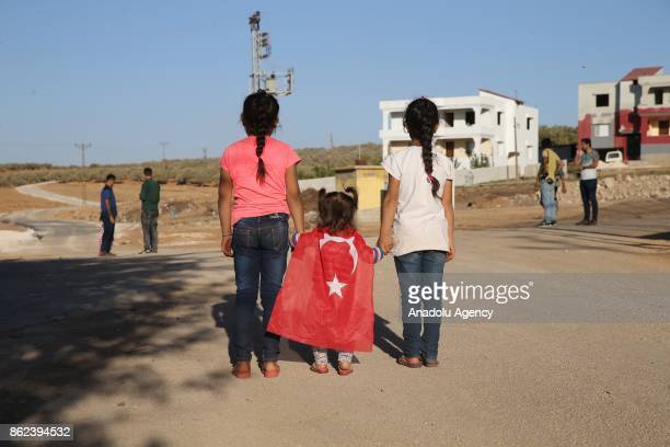 Children hold hands of a little girl wearing a Turkish flag during Turkish Army's armoured vehicles' deployment to the border line in the Turkish...