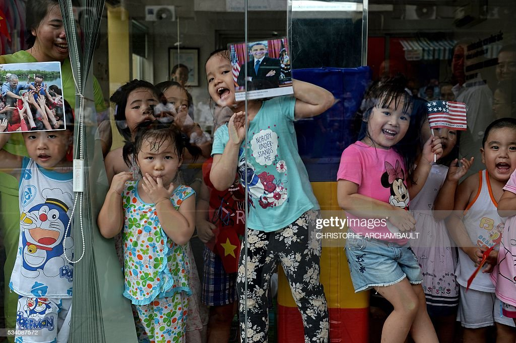Children hold pictures of US President Barack Obama as people line up the streets to catch a glimpse of the US leader on his way to the airport at the end of two-day visit to Ho Chi Minh City on May 25, 2016. Obama fielded questions on May 25 on everything from rap and weed smoking to leadership and his good looks at a lively town hall-style meeting with young Vietnamese, who say the US leader is a far cry from their staid Communist rulers. / AFP / CHRISTOPHE
