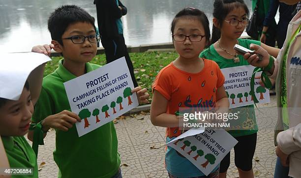 Children hold placards as they and their families join a rally protesting against a treefelling plan by the municipal authorities in Hanoi on March...