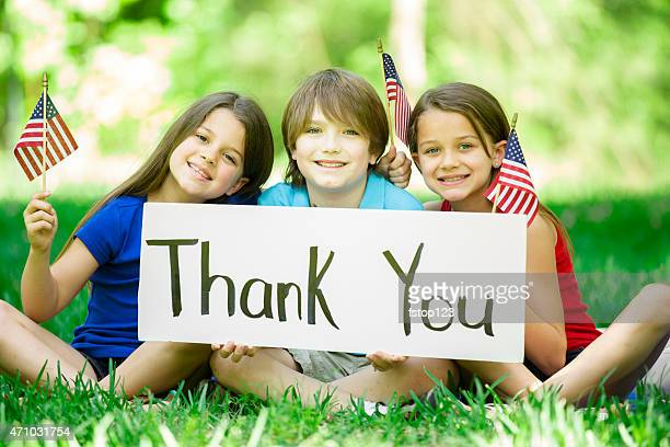 Children hold 'Thank You' sign with American flags. Memorial Day.