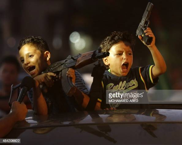 Children hold up guns from a car as Palestinians gather in the streets to celebrate after a deal had been reached between Hamas and Israel over a...