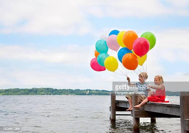 Children holding balloons on wooden pier