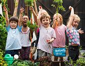Children holding carrot in a garden