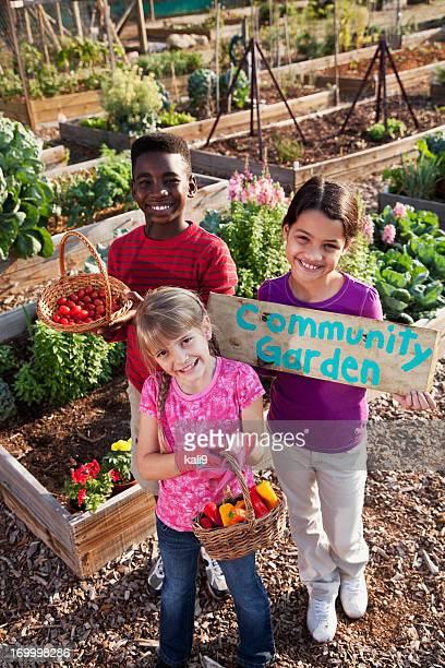 Children holding community garden sign