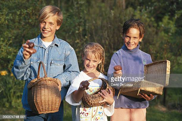 Children (6-11) holding  Easter chocolate with basket, smiling