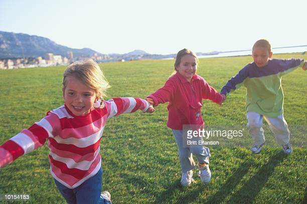 Children (4-8) holding hands, running on grass