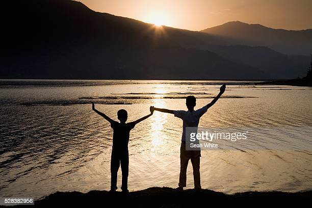 Children holding hands stretched up to the sky