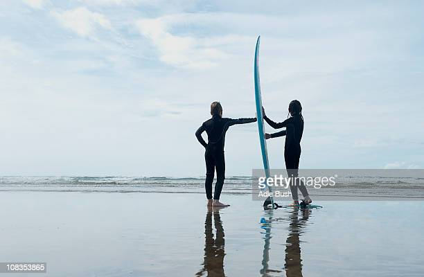 Children holding surf board on beach