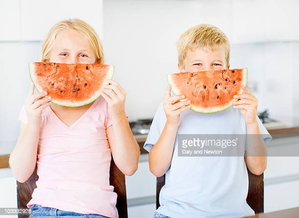 Children holding watermelon slice in front of face
