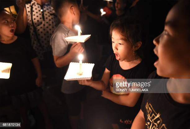 Children holds candles in support for Basuki Tjahaja Purnama known by his nickname Ahok to give their support for his freedom from the accused of...