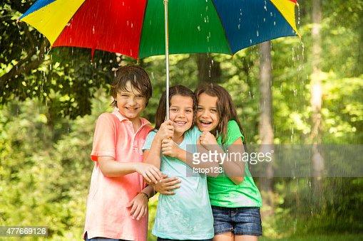 Enfants se regrouper sous parapluie en plein air sous la pluie.