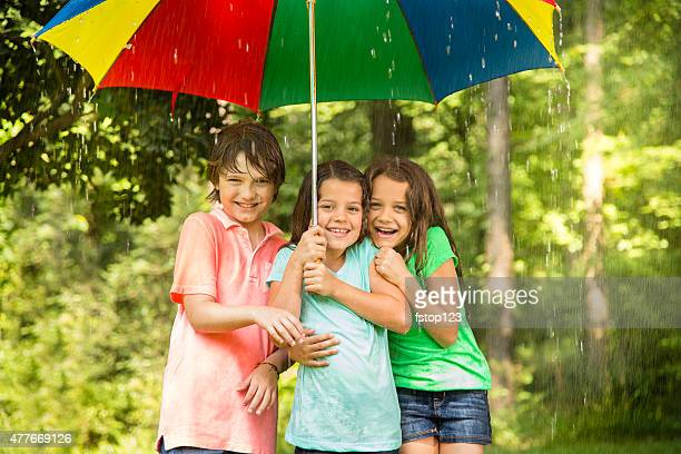 Children huddle under umbrella outdoors in rain.
