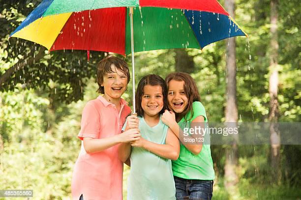 Kinder Gruppe bilden unter Regenschirm draußen im Regen.