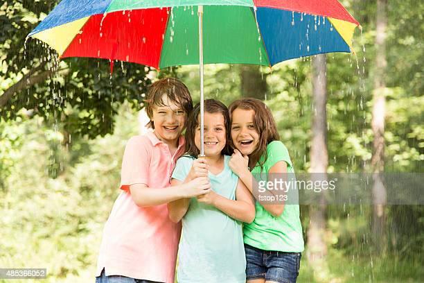 Children huddle under umbrella outdoors in rain.