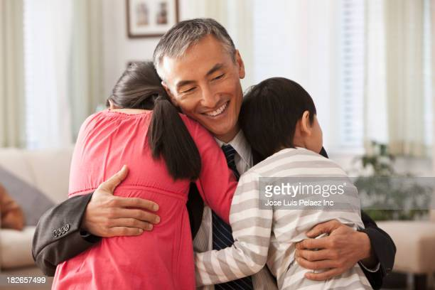 Children hugging father in living room