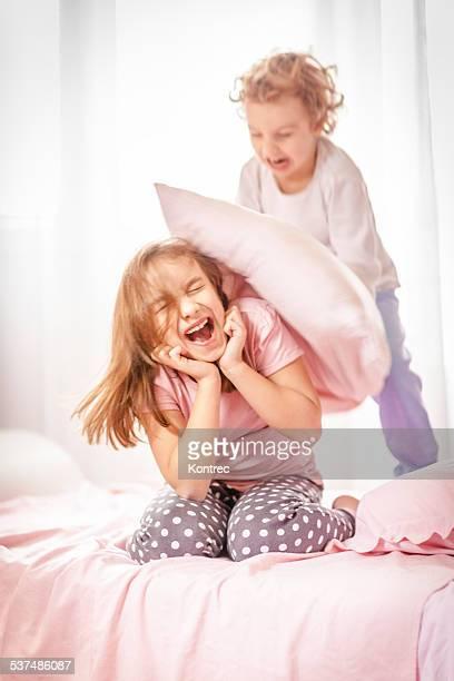 Niños en una lucha con almohada