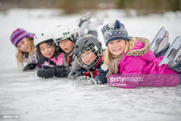 Children in a Row Playing on the Ice