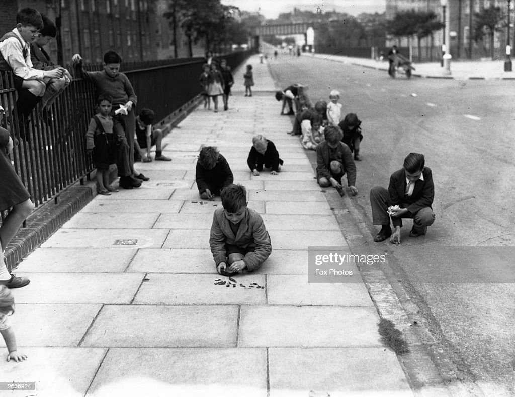 Children in a street in South London sorting shrapnel, anti-aircraft shell fragments, which they have collected as their contribution to the national war effort.