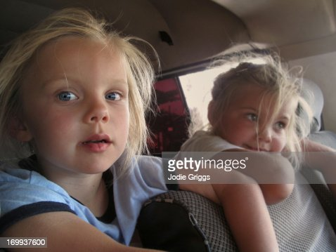 Children in back of a van leaning over front seats