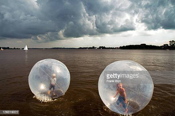 Children in balls on water