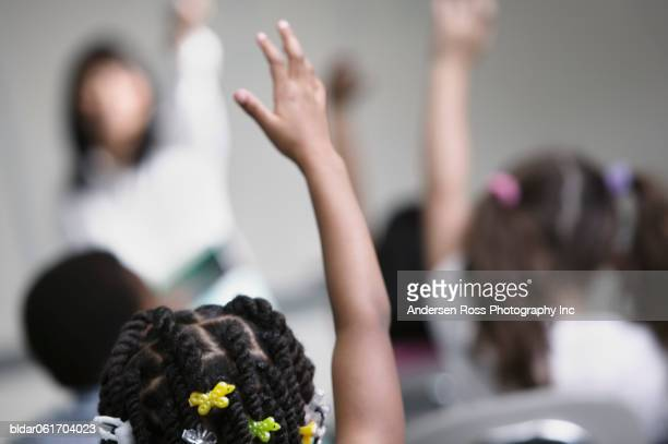 Children in class with raised hands