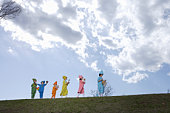 Children (4-13) in colorful costume playing musical instruments in park
