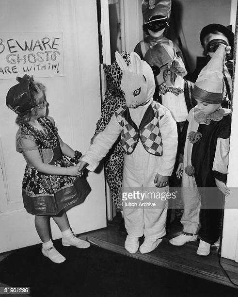 Children in costumes arriving at a Halloween party USA circa 1955 A sign on the door warns 'Beware Ghosts are within'