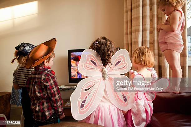 Children in costumes watching television