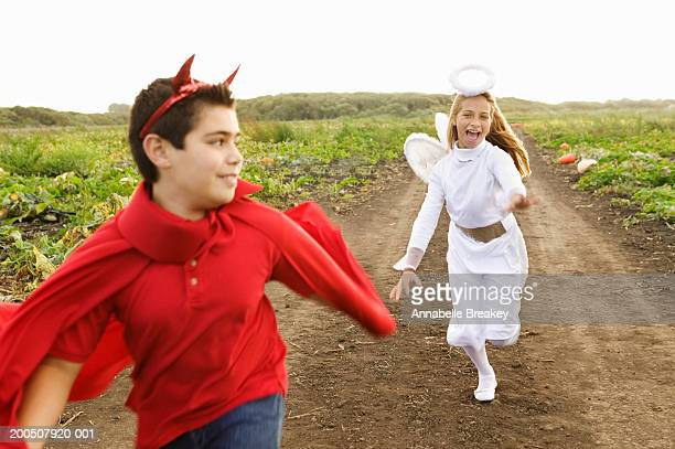 Children (10-12) in devil and angel costumes running in field