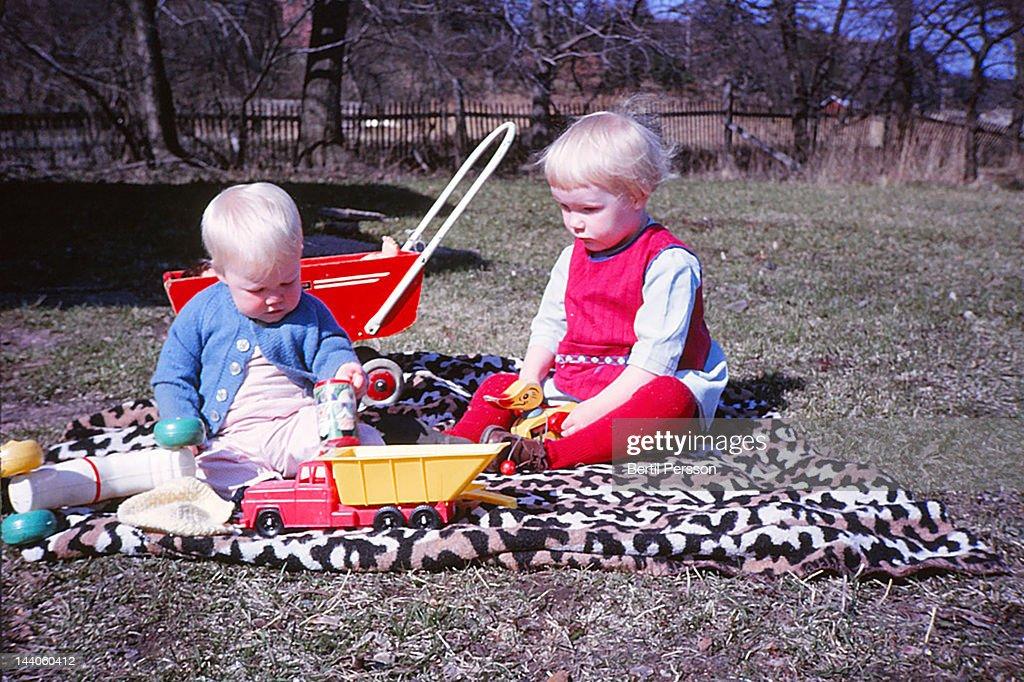 Children in garden on rug : Stock Photo