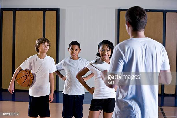 Children in gym with physical education teacher or coach