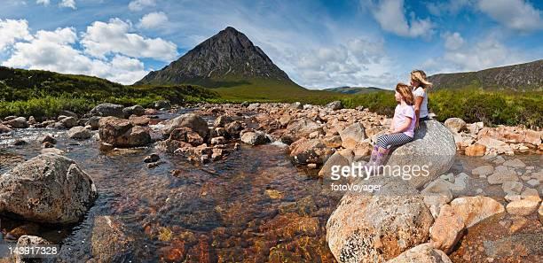Children in idyllic panoramic mountain stream wilderness