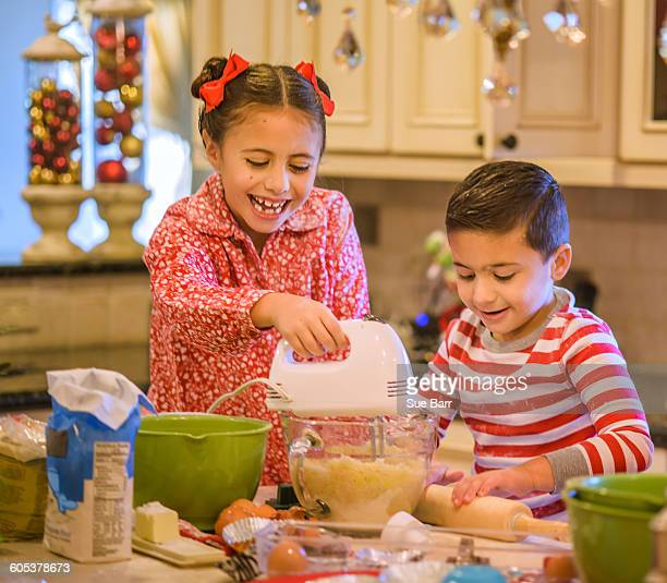 Children in kitchen wearing pyjamas using hand mixer on cookie dough smiling