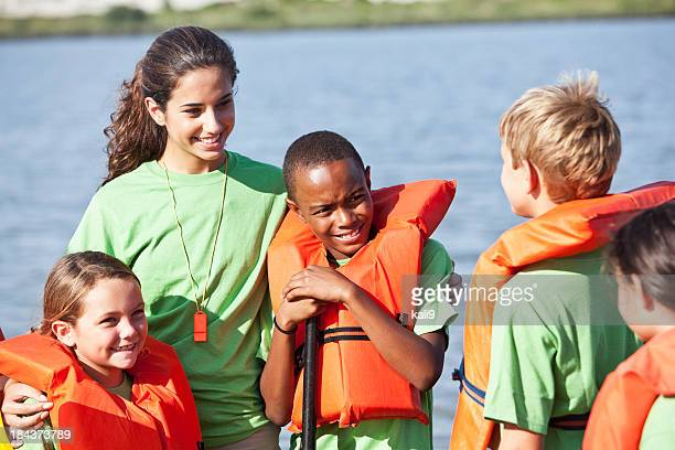 Children in life jackets with young woman at camp