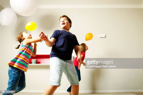 Children in living room playing with balloons, Munich, Bavaria, Germany