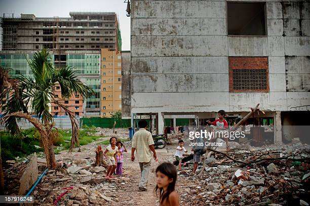Children in one of Phnom Phen's slums use a site of ruined buildings which used to be their home as their playground Land grabbing becomes a more...