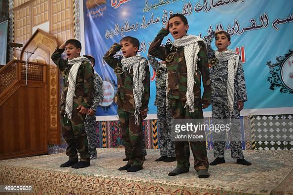 Children in paramilitary dress recite Shia Islamic scripture in the compound of the alAskari shrine on April 9 2015 in Samarra Iraq The shrine was...