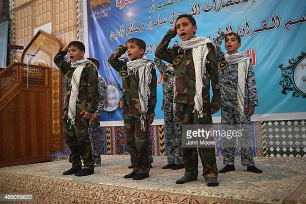 Children in paramilitary dress recite Shia Islamic scripture in the compound of the alAskari shrine on April 9 2015 in Samarra Iraq The shrine was...