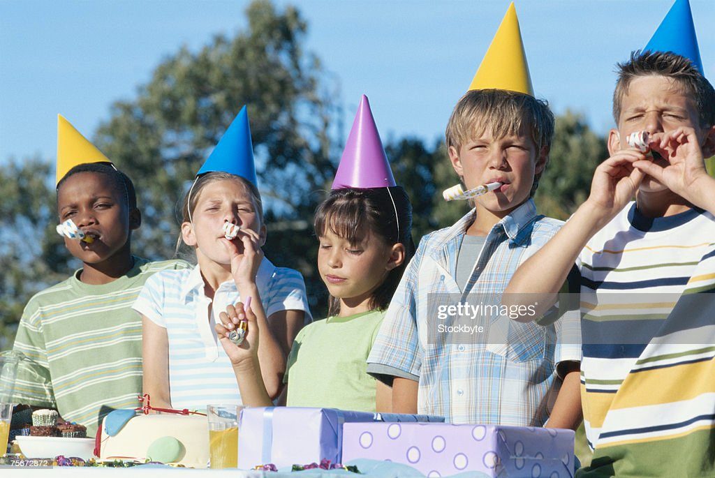 Children (4-9) in party hat blowing party horn blower