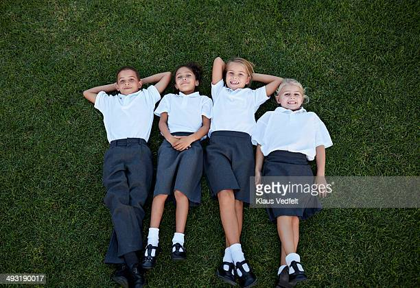Children in school uniforms laying on grassfield