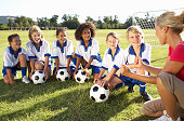 Group Of Children In Soccer Team Having Training With Female Coach